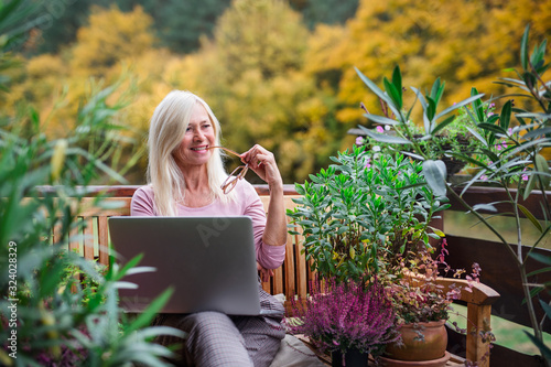 Photo Senior woman with laptop sitting outdoors on terrace, working.