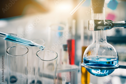 Cuadros en Lienzo dropping liquid to test tube containing chemical liquid in laboratory, lab chemistry or science research and development concept