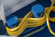 Yellow Ship Rope Tied Around Blue Mooring Bollards On A Boat Deck