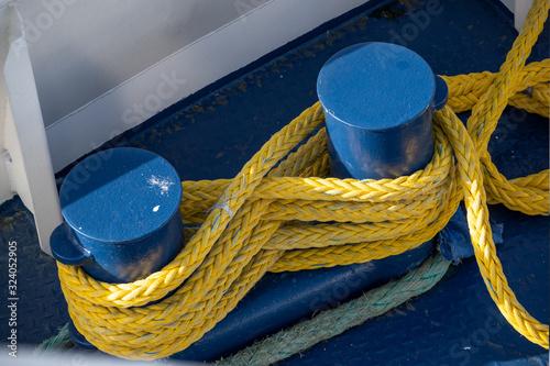 Fotografia yellow ship rope tied around blue mooring bollards on a boat deck