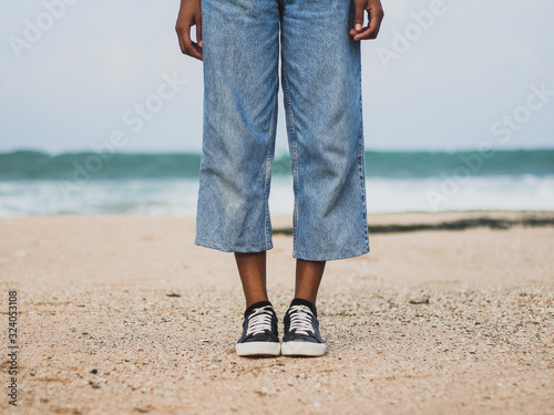 Fotografie, Tablou Girl wearing denim pants, pair of blach shoes with white borders, white cords an