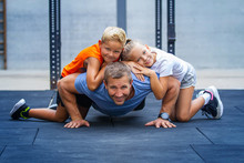 Happy Family Exercising Together In Gym
