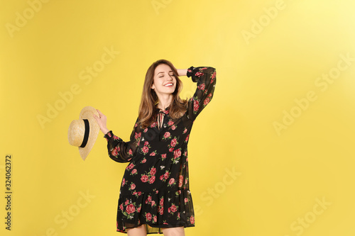 Young woman wearing floral print dress with straw hat on yellow background