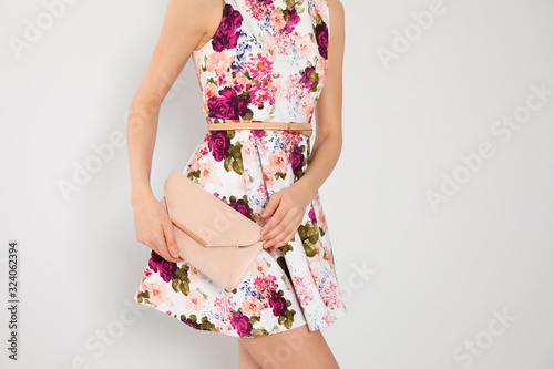 Young woman wearing floral print dress with clutch on light background, closeup