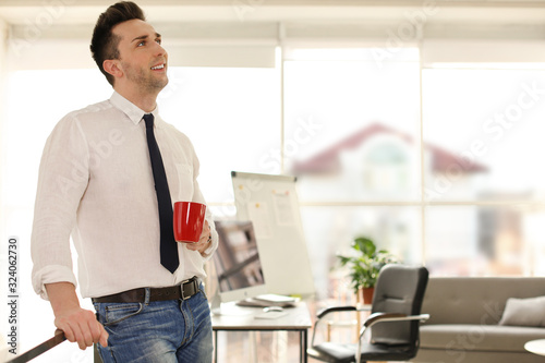Young businessman with cup of drink relaxing in office during break