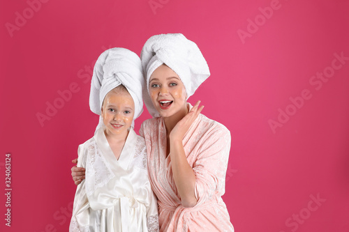 Emotional mother and daughter with facial masks on pink background