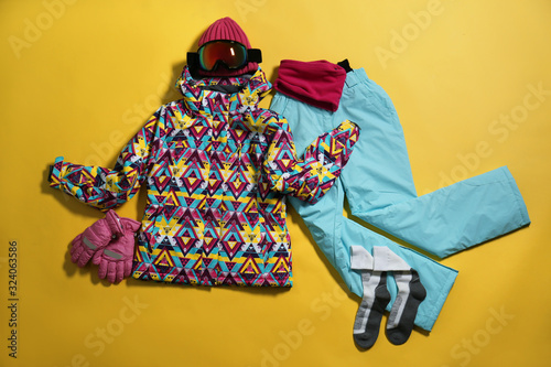 Stylish winter sport clothes on yellow background, flat lay