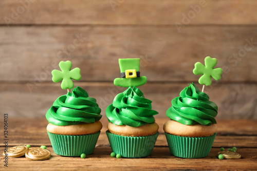 Decorated cupcakes and coins on wooden table. St. Patrick's Day celebration