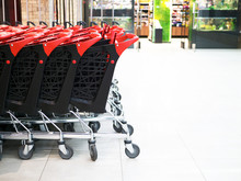 Stack Of Many Plastic Shopping Cart Trolley With Each Other In A Row. Black And Red Supermarket Cart On Wheels. Mall Concept Consumer Business. Store Consuming, Grocery Shopping