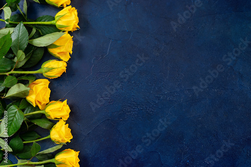 Obraz Top view of beautiful yellow roses on dark blue background - fototapety do salonu