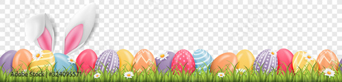 Foto Easter bunny ears with easter eggs on meadow with flowers background banner tran
