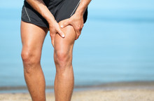 Sports Injury Muscle Cramp Pain Fit Runner Man Athlete Holding Painful Thigh Leg On Outdoor Summer Jogging Exercise. Fitness Lifestyle.