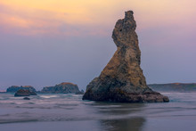 Long Exposure Image Of Waves Breaking On The Beach Near Howling Dog Rock At Sunset In Bandon, Oregon.