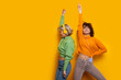 Two gorgeous caucasian girls dancing on a yellow background while listening to music through headphones