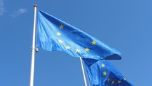 Two EU Flags Waving Freely On Flagpole In Celeste Sky In Spring In Slow Motion