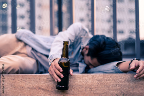 Fotografie, Obraz Asian drunk man holding beer bottle lying on floor