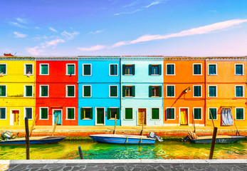 Burano island canal, colorful houses and boats in the Venice lagoon. Italy