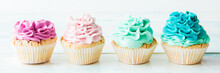 Four Colorful Cupcakes On A Light Background. Copy Space
