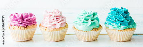 Four colorful cupcakes on a light background. Copy space Wallpaper Mural
