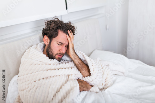 Photographie Man being sick having flu lying in bed checking his temperature and drinking hot beverage