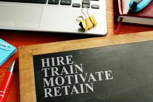 Staff Hire, Train, Motivate And Retain Written On The Blackboard.