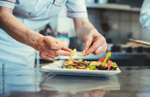 Fototapeta Proud chef garnishing an almost finished dish in the restaurant with leave