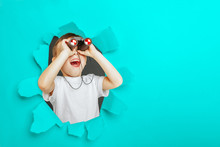 Happy Cute Boy Is Having Looking Through Binoculars Through A Torn Hole In Turquoise Paper