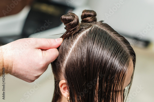Hairdresser working with wet woman's hair during making hairstyle, close up.
