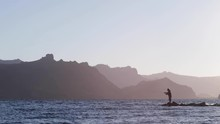 Silhouette Of Man Fishing Off Natural Rock Peninsula Surrounded By Choppy Water And Cliffs