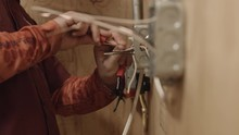 An Electrician Twists Wires Wo...