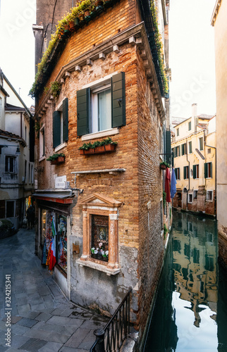 Fotomural View of the thin colorful house between canal and street in Venice, Italy