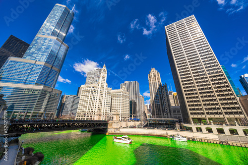 Fototapeta Chicago building and cityscape on Saint Patrick's day around Chicago river walk with green color dyeing river in Chicago Downtown, illinois, USA, crowned irish and american people are celebrating. obraz