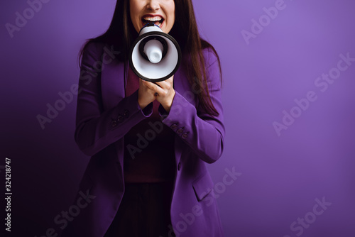 Photo cropped view of excited woman screaming in megaphone on purple background