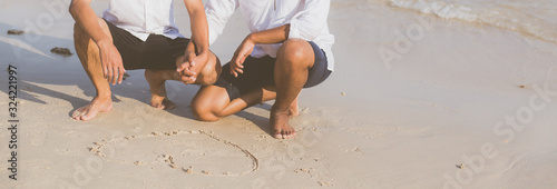 Photo Young asian couple gay romantic drawing heart shape together on sand in vacation, homosexual happy and fun with love sitting on sand at the beach in travel summer, LGBT legal concept, banner website