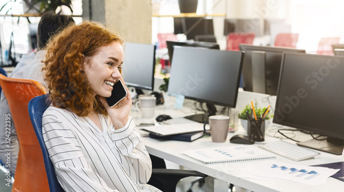 Smiling young woman talking by phone with clients