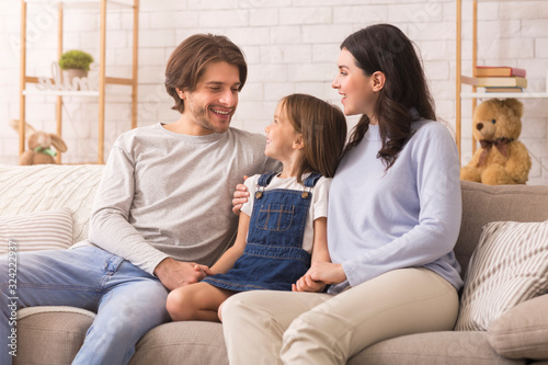 Young man and woman bonding with their little daughter at home