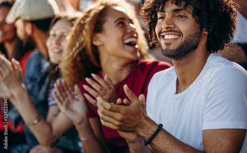 Fototapeta Man clapping while watching a soccer match with friends at stadi obraz