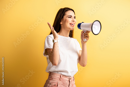 happy girl speaking in megaphone while standing with open arm and looking away o Canvas Print