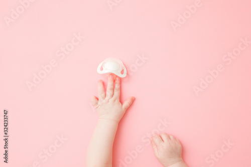 Fototapeta Infant hand reaching after white soother on light pink floor background