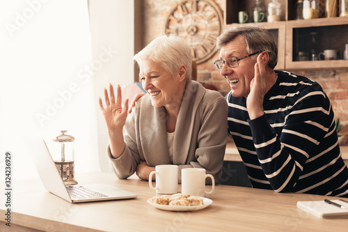 Obraz Happy senior couple looking at laptop screen in kitchen and waving - fototapety do salonu