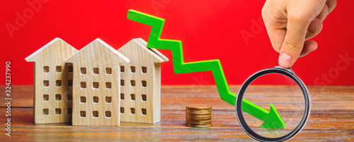 Fototapeta Miniature wooden houses and a green arrow down. The concept of low cost real estate. Lower mortgage interest rates. Falling prices for rental housing and apartments. Reducing demand for home buying obraz