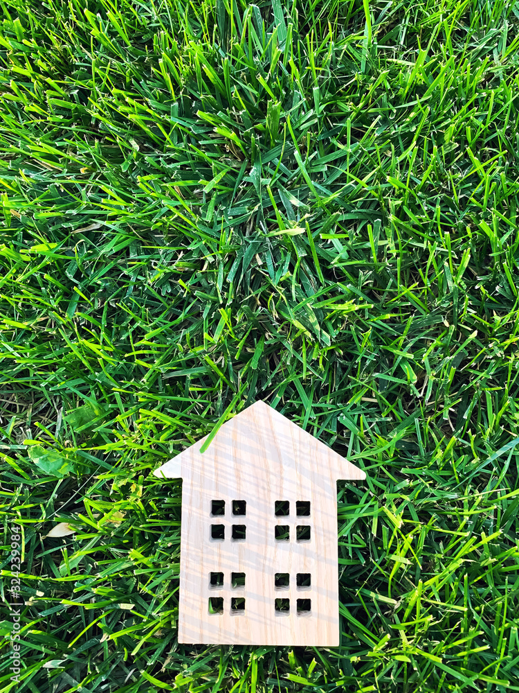 Fototapeta Miniature wooden house on green grass. Real estate concept. Modern housing. Eco-friendly and energy efficient house. Buying a home outside the city. Nature. Fresh air. Mortgage, loan. Place for text.