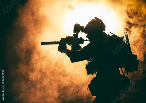 Silhouette of modern infantry soldier, elite army fighter in tactical ammunition and helmet, standing with assault service rifle in hands on background of fiery explode Tapéta, Fotótapéta