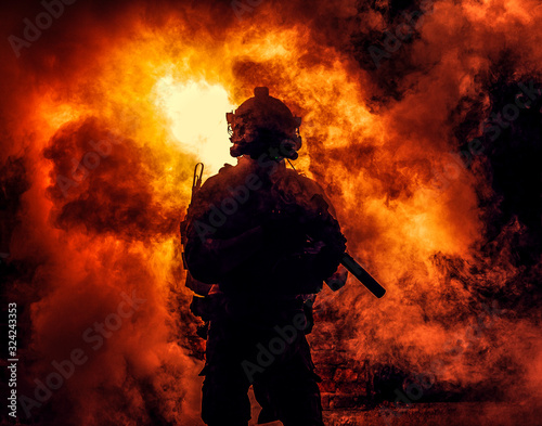 Fényképezés Silhouette of modern infantry soldier, elite army fighter in tactical ammunition and helmet, standing with assault service rifle in hands on background of fiery explode