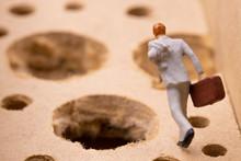 沢山の落とし穴を避けながら走るビジネスマン