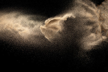 Brown colored sand splash.Dry river sand explosion isolated on black background. Abstract sand cloud.