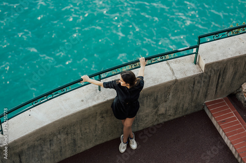 Stylish happy girl enjoying the azure water of Mediterranean sea standing at the cliff on Cote d'Azur, Monaco Canvas Print
