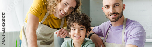 Leinwand Poster panoramic shot of mixed race kid near happy homosexual parents