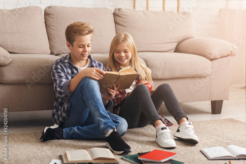 Fototapeta Siblings Reading Book Learning Together Sitting On Floor Indoor obraz