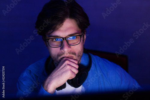 Thoughtful Developer Looking At Computer Screen Working From Home, Low-Light Wallpaper Mural